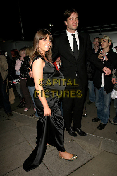CLAUDIA WINKLEMAN & GUEST.Leaving the British Academy Television Awards (Bafta's),.Grosvenor House Hotel, London, England, May 7th 2006..bafta baftas full length black satin dress pregnant flat gold sequined pumps shoes.REf: AH.www.capitalpictures.com.sales@capitalpictures.com.©Adam Houghton/Capital Pictures.