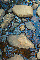 Rocks positioned in a small creeek traversing a hiking trail in the Rocky Mountain National Park in Colorado.