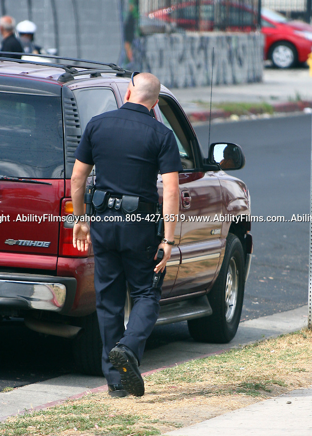 August 2nd 2011..Jake Gyllenhaal dressed up in a police uniform holding a gun at a suspect while filming his movie End of Watch in Los Angeles. Jake has a bald shaved head & loves playing a cop. ..AbilityFilms@yahoo.com.805-427-3519.www.AbilityFilms.com.