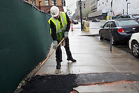 David Dollosa repairs a sidewalk with asphalt while working for the Boston Public Works Department in Boston, Massachusetts, USA, on April 12, 2012. The city uses a computer system to track public complaints and record work done by city crews to mitigate these complaints.  A supervisor or inspector photographs before and after pictures of the work in addition to making notes about the work done.