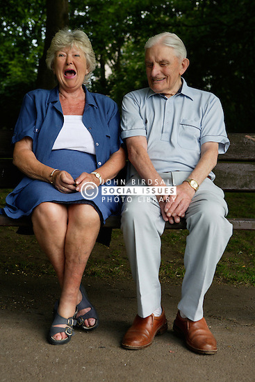 Older couple sharing a joke whilst sitting on a bench in the park ,
