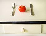 Tomato, knife and fork stillife.