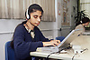 Young girl with visual impairment sitting at desk in office using keyboard with audio feedback device,
