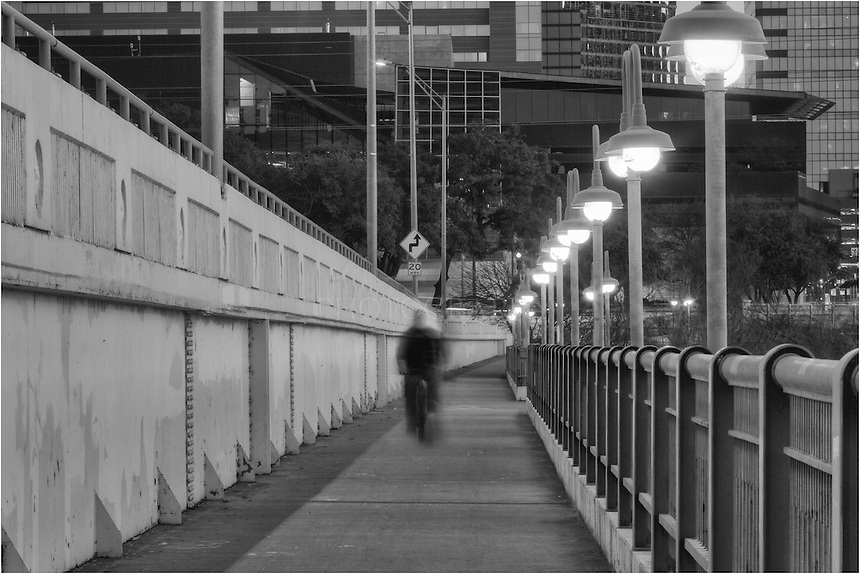 On an early Friday morning, a bicycler commutes across the 1st Street Bridge in downtown Austin, Texas.  Below the bridge is Ladybird Lake. Surronding Ladybird Lake are miles of trails to ride, walk, run, or just enjoy the beautiful Austin weather.