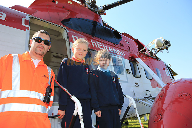 Grace O'Brien and Breena Vaughan with Officer Earl Gorman Pictured during the visit of the Irish Coast Guard Helicopter from Dublin Airport with members of the Irish Coast Guard Drogheda at Whitecross national school in Julianstown Co Meath.<br /> Picture:  Fran Caffrey / www.newsfile.ie