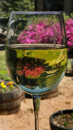 "A glass of white wine inverts the image of the grounds of Taverna Winery & Restaurant in Conroe. Marigolds, oregano, mint, spearmint, English thyme, and lemon thyme are among the herbs growing in barrels on the grounds. Chef Jimmy Mitchell, the new executive chef at Taverna Winery & Restaurant is also a master gardner. He has started a ""kitchen friendly"" garden that he can use to help supply his kitchen. (Thursday, March 20, 2008, in Conroe. ( Steve Campbell / Houston Chronicle)"