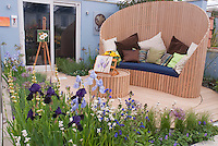 Painting in the garden, with easel, watercolor, irises, bench seat and table furniture next to house sliding doors