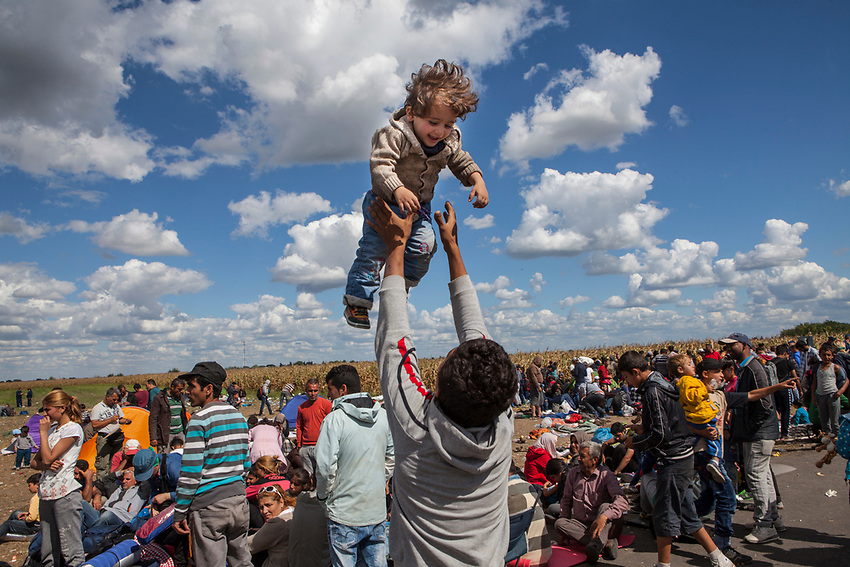 A father plays with his daughter while waiting to board a bus. Refugees at Roszke Crossing on Serbian-Hungarian Border.