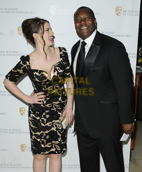 HAYLEY ATWELL & LENNY HENRY.British Academy Television Craft Awards at the Hilton, Park Lane, London, England. .May 23rd 2010 .BAFTA half 3/4 length sleeves black gold cream patterned pattern dress hand on hip white clutch bag profile laughing smiling suit.CAP/CAN.©Can Nguyen/Capital Pictures.