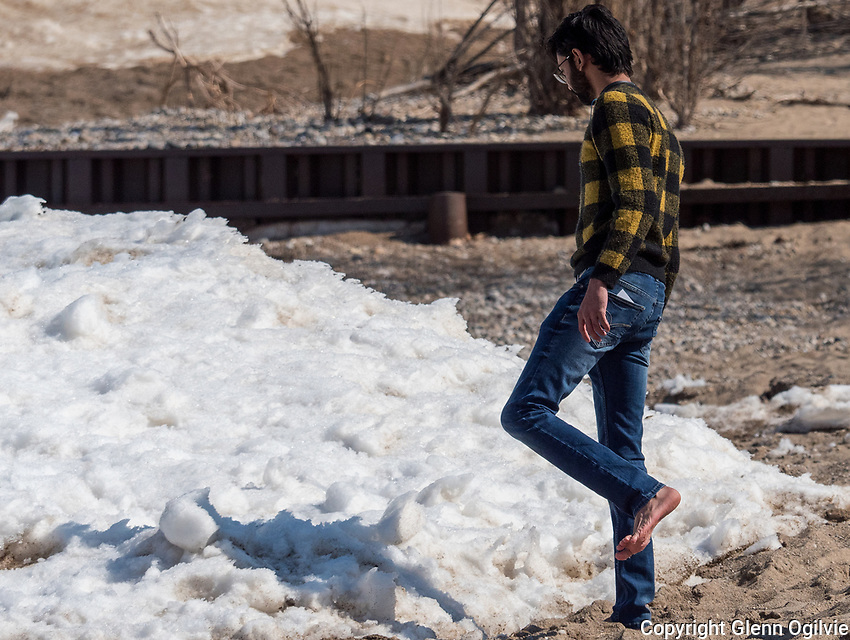 Sarnia residents Gaurang Patel, black coat, and Milansinh Vaghela, both Lambton College students take a break from studies to explore the ice along the shore of Lake Huron. Milansinh braved the cold to walk barefoot in the sand.