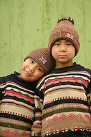 On the road to Akesu City in China's Xinjiang Uyghur Autonomous Region, our bus stopped in a small town with a supermarket where I made friends with two young boys in matching sweaters and hats with a Union Jack.