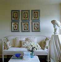 A series of framed engravings depictng theatrical costumes hangs above a white sofa in the living room