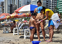 RECIFE, PE, 24 DE FEVEREIRO 2013 -CLIMA TEMPO PRAIA DE BOA VIAGEM - Criança recebe pulseira com nome e contato do responsável para facilitar identificacação em caso de perda na orla da Praia de Boa Viagem, zona Sul do Recife. FOTO LÍBIA FLORENTINO - BRAZIL PHOTO PRESS.