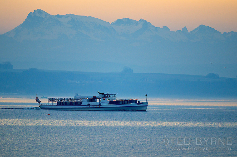 Passenger boat crossing the Lake of Neuchâtel with the Swiss Alps in the distance