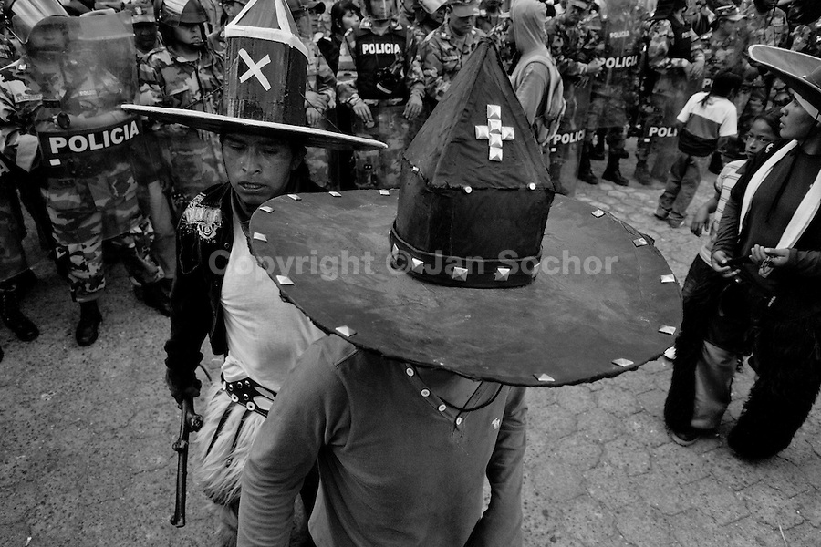 Indians, wearing cardboard hats, dance in front of the police block during the Inti Raymi (San Juan) festivities in Cotacachi, Ecuador, 24 June 2010. 'La toma de la Plaza' (Taking of the square) is an ancient ritual kept by Andean indigenous communities. From the early morning of the feast day, various groups of San Juan dancers from remote mountain villages dance in a slow trot towards the main square of Cotacachi. Reaching the plaza, Indians start to dance around. They pound in synchronized dance rhythm, shout loudly, whistle and wave whips, showing the strength and aggression. Dancers from either the upper communities (El Topo) or the lower communities (La Calera), joined in respective coalitions, seek to conquer and dominate the square and do not let their rivals enter. If not moderated by the police in time, the high tension between groups always ends up in violent clashes.