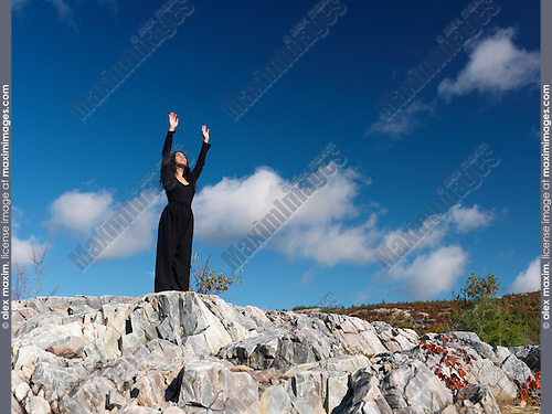 Young asian woman standing on rocks and facing the sun with her arms raised, practicing sunrise Qi Gong, moving meditation. Ontario, Canada.