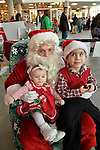 Garden City, New York, USA. November 30, 2013. Summer, 7-month-old baby girl, and her big brother Sawyer, 4, of Long Beach, visit with Santa Claus at the Winter holiday event Festival of Trees, held at Cradle of Aviation Museum during Thanksgiving weekend, with proceeds benefiting United Cerebral Palsy Association of Nassau County, Long Island.