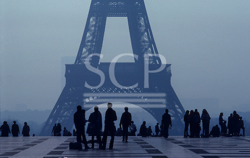 Paris, France. The Eiffel Tower with people on a paved area on a misty day.