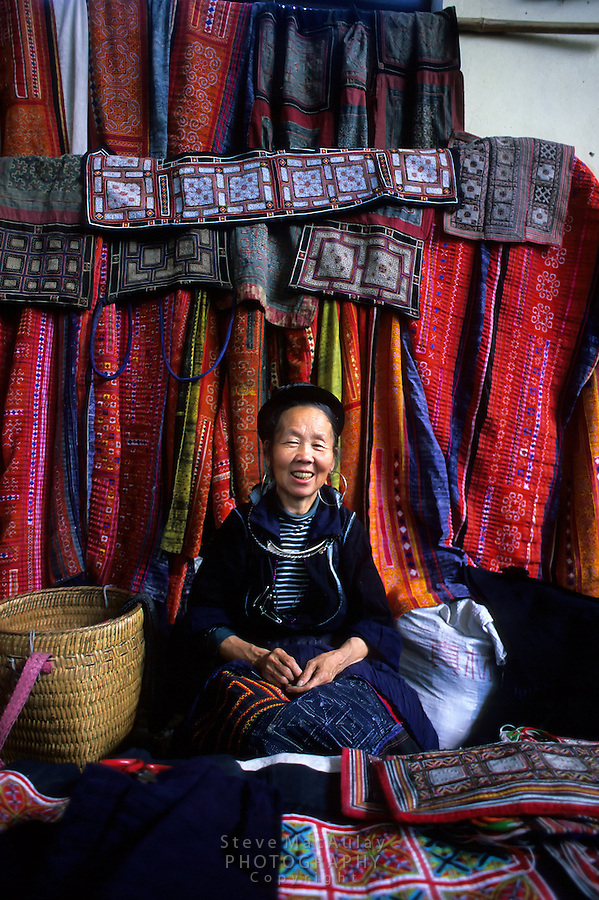 Black H'mong Woman selling colorful woven goods at the Saturday market, Sapa, Vietnam.