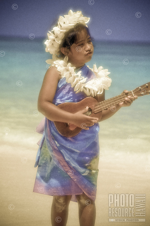 Young Hawaiian girl practicing the ukulele at the beach with leis on