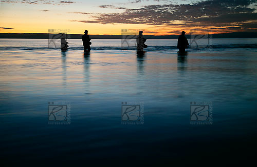 Trout fishermen fishing the Waitahunui river mouth at sunset, Lake Taupo, Waikato, New Zealand