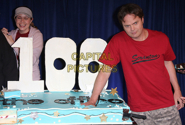 "JENNA FISCHER & RAINN WILSON.""The Office"" 100th Episode Celebration held at Calamigos Ranch, Malibu, California, USA..April 14th, 2009.half length cake food icing pink tracksuit top hat red t-shirt hand funny .CAP/ADM/KB.©Kevan Brooks/AdMedia/Capital Pictures."
