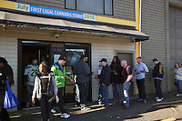 USA. Washington state. Seattle. Customers wait in line to enter Cannabis City while a security man controls their ID cards before entering the shop. Weed products are available to anyone aged 21 years and older. Cannabis City is authorized, according to cannabis legalization in Washington State, to sell marijuana as a retail store front. Cannabis City was the first state-licensed store for recreational marijuana open in July 2014. Cannabis, commonly known as marijuana, is a preparation of the Cannabis plant intended for use as a psychoactive drug and as medicine. Pharmacologically, the principal psychoactive constituent of cannabis is tetrahydrocannabinol (THC); it is one of 483 known compounds in the plant, including at least 84 other cannabinoids, such as cannabidiol (CBD), cannabinol (CBN), tetrahydrocannabivarin (THCV), and cannabigerol (CBG). 14.12.2014 © 2014 Didier Ruef