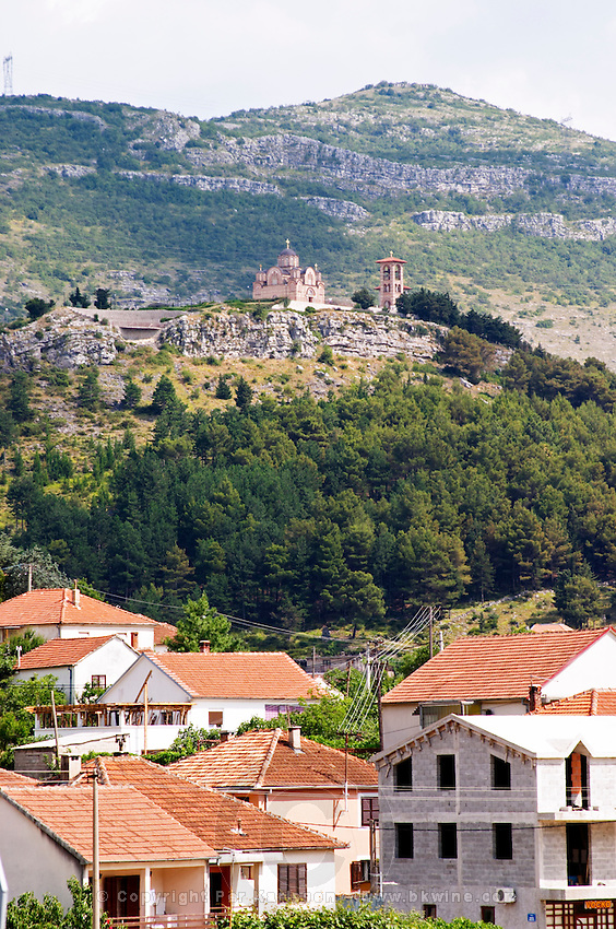 Street scene in Trebinje, the monastery Gracanica on the historic hill known as Crkvina in the background. Houses and construction sites. Trebinje. Republika Srpska. Bosnia Herzegovina, Europe.