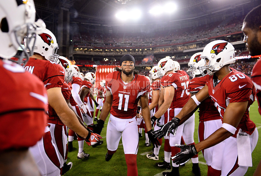Aug. 30, 2012; Glendale, AZ, USA; Arizona Cardinals wide receiver (11) Larry Fitzgerald is greeted by teammates during player introductions prior to the game against the Denver Broncos during a preseason game at University of Phoenix Stadium. Mandatory Credit: Mark J. Rebilas-