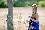 A beautiful blond young woman stands outdoors in a park in the summer.