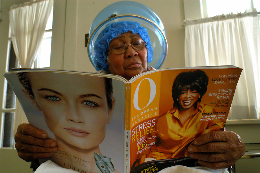 Rosemary Evans reads a magazine as she waits in the Rhineharts' Barbershop in Muncie. Though the Rhineharts retired several years ago, loyal customers, such as Evans, convinced them to continue to work one day a week.