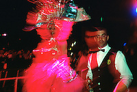 A waiter serves a beer as scantily clad entertainers parade down the aisles through the audience at the Tropicana nightclub. The dancers entertain at the infamous pre-Revolutionary cabaret wearing flamboyant headdresses with glowing chandeliers and ostentatious sequined outfits embellished with feathers. Since New Years 1939, the show has featured more than 200 performers in dance and song numbers on stages at various outdoor stages
