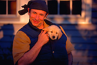 Portrait of a smiling middle-aged man holding his golden retriever puppy inside his down vest.