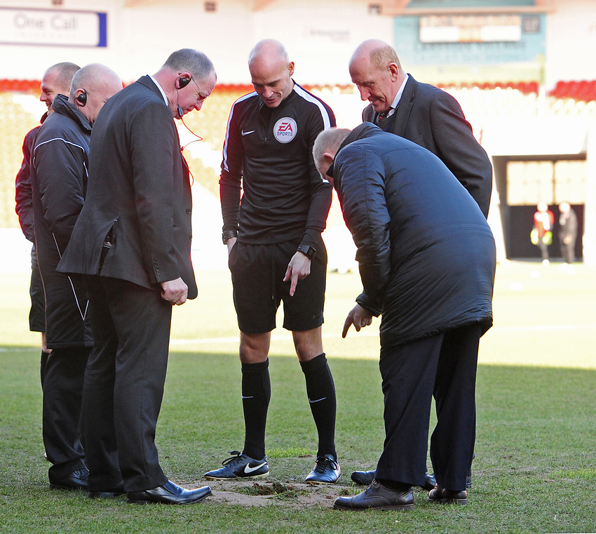 Referee Darren Drysdale, centre, and officials look at a hole that appeard in the pitch at Doncaster Rovers Keepmoat Stadium during the pre-match warm-up<br /> <br /> Photographer Chris Vaughan/CameraSport<br /> <br /> The EFL Sky Bet League One - Doncaster Rovers v Fleetwood Town - Saturday 17th February 2018 - Keepmoat Stadium - Doncaster<br /> <br /> World Copyright © 2018 CameraSport. All rights reserved. 43 Linden Ave. Countesthorpe. Leicester. England. LE8 5PG - Tel: +44 (0) 116 277 4147 - admin@camerasport.com - www.camerasport.com