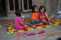 Borobudur, Java, Indonesia.  Young Javanese Girls Sitting on the Porch of their Rural Home.