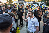 Avi Yemini, a supporter of the anti-Islamic Australian Liberty Alliance, argues with young Muslim men in front of police vehicles at Speakers' Corner, Hyde Park, London.