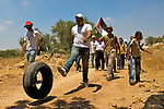 A Palestinian kicks along a tyre as Palestinian, Israeli & international activists march to a gate in Israel's controversial separation barrier built on Palestinian land in the village of Ni'lin near Ramallah on 16/07/2010.