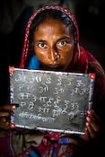 Miriam Nasah poses with her blackboard in a classroom  where local village women attend SHG (self help group) literacy programme organised by the Fakirana Sisters Society in Vishambarpur Village, in Bettiah of West Champaran district in Bihar. Since 2008 the Foundation and Geneva Global have been investing in the training of medical staff to improve the lives of people living in 600+ villages in the region. The NGOs are delivering cost effective interventions to address treatment, care and prevention of diseases, disability and preventable deaths amongst infants, adolescent girls and women of child-bearing age. There is statistical and anecdotal evidence that there have been vast improvements and a total of 40-50% increased immunization for all children under 6 has meant that communities can be serviced and educated long term. Photograph: Sanjit Das/Panos for Legatum Foundation