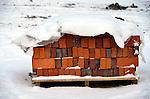 Bouwdetails tijdens een koude vorstperiode op een bouwplaats in de winter: ondersneeuwde stenen liggen klaar om te verwerkt te worden door metselaar voor afbouw.  COPYRIGHT TON BORSBOOM