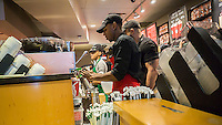 Starbucks workers during the Starbucks Cheer promotional event in New York on Wednesday, December 28, 2016. For the 10 days, excluding Christmas, Starbucks is giving away a tall espresso drink of your choice between the hours 1 and 2PM at a rotating choice of 100 stores around the country. (© Richard B. Levine)