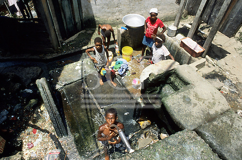 Rio de Janiero, Brazil. Shanty town, young boy having a shower, girls waiting with thier washing for water at the communal tap.
