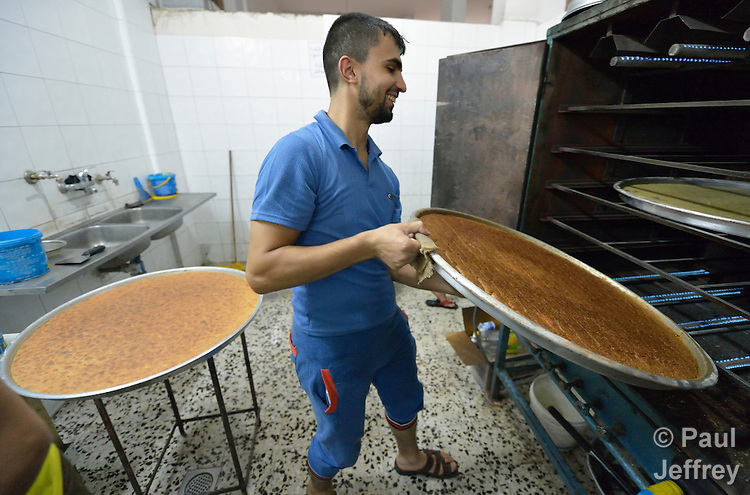 A man bakes namoura, a sweet pastry, in the Zeitoun neighborhood of Gaza City, Gaza. Residents of the Palestinian territory are still reeling from the death and destruction of the 2014 war with Israel, and the continuing siege of the seaside territory by the Israeli military.
