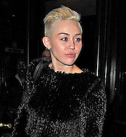 Miley Cyrus with a fuzzy black sweater with a pleated skirt in New York City