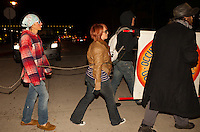 Ken (left), Charlie (center), and Justin (right) march at South Coast Plaza for Occupy Orange County early in the morning of Black Friday.  The protesters were tied together by rope, being led by a single protestor dressed in a suit (as a banker), symbolizing how the 1% lead the 99%.