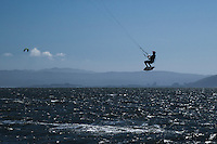 An airborne kiteboarder flies over San Francisco Bay along Crown Memorial State Beach in Alameda, California.