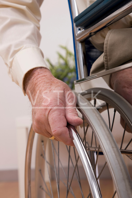 Close-up of senior man's hand on wheel chair