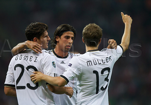 07.10.2011 Istanbul Turkey.  Germany's Mario Gomez (L) and Sami Khedira (C) and Thomas Mueller (R) celebrate after Gomez scored the 1-0 during the EURO 2012 qualifying match between Turkey and Germany at the Turk Telekom Arena.