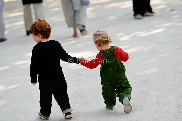 Two young brothers walking in a park holding hands.