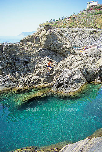 A boy flies off of a rock into the blue sea at Manarola, in the Cinque Terre, Italy.