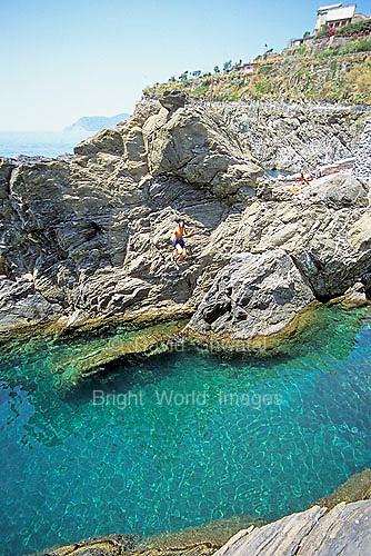A boy flies off of a rock into the blue sea at Manarola, in the Cinque Terre, Italy.